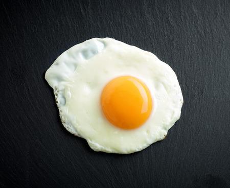 Huevo frito en el fondo de piedra negro Foto de archivo - 63073572