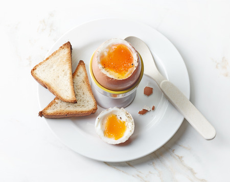 freshly boiled brown egg on white plate, top view
