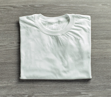 a shirt: white folded shirt on grey wood background, top view