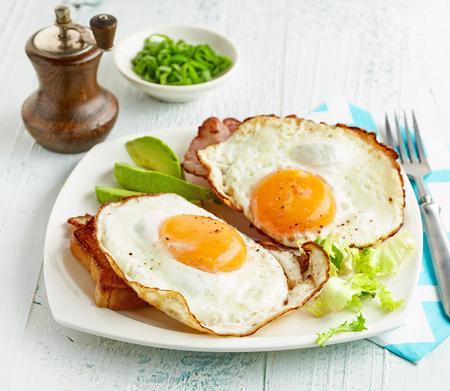 huevos estrellados: huevos fritos, pan y tocino en un plato blanco