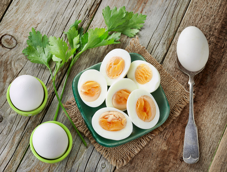 various boiled eggs on old wooden table, top view