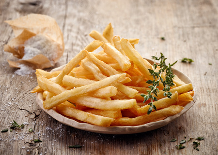 plate of french fries on wooden table Stockfoto