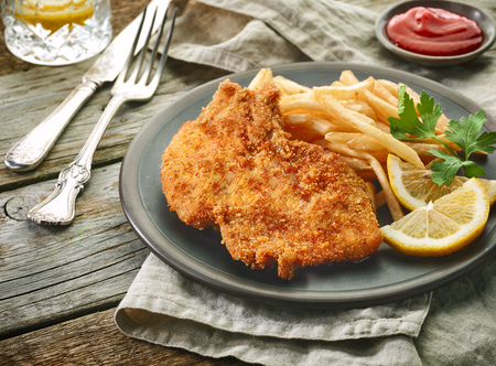 pork schnitzel and fried potatoes on wooden table Archivio Fotografico