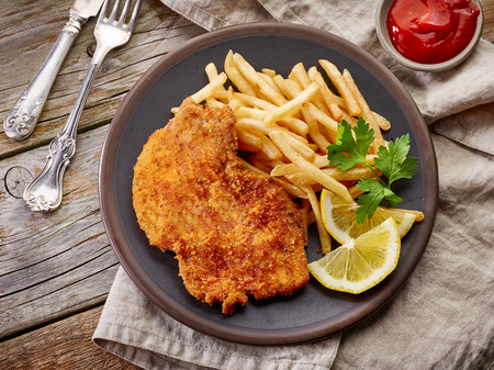 schnitzel and fried potatoes on dark plate, top view