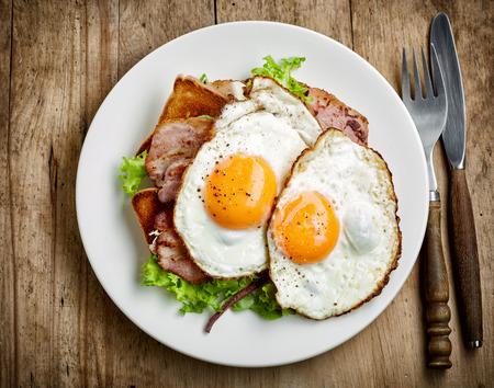 huevos fritos: plato de huevos fritos y tocino en un plato blanco, vista desde arriba Foto de archivo
