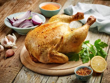 Gehele geroosterde kip op houten keukentafel