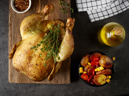 whole roasted chicken on wooden cutting board, top view