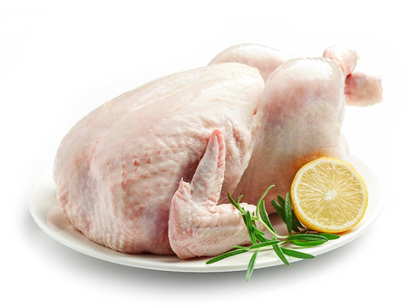 whole raw chicken on plate isolated on white background