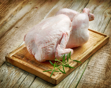 whole raw chicken on wooden cutting board