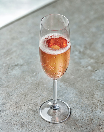 glass of pink champagne on grey table