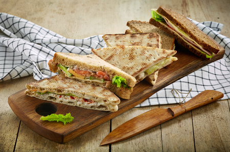 half fish: various triangle sandwiches on wooden cutting board