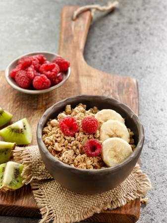 breakfast bowl: bowl of breakfast granola with banana and raspberries on wooden board Stock Photo