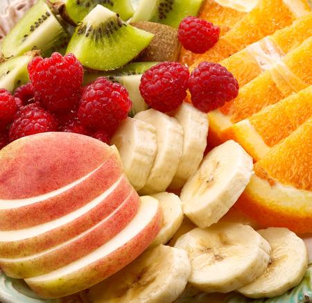 ensalada de frutas: Cerca de piezas de fruta y frambuesas Foto de archivo