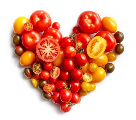 heart shape by various tomatoes isolated on white background