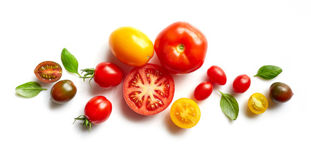 various colorful tomatoes and basil leaves isolated on white background