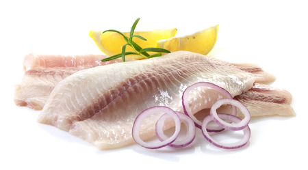 fillets: fresh raw bream fish fillets with onions and lemon slices isolated on white background