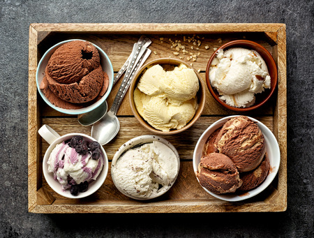 bowls of various ice creams on dark gray table, top view Stockfoto