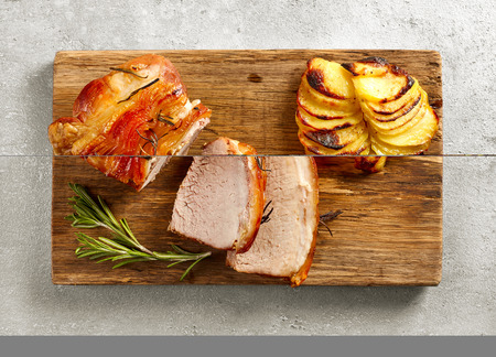 cutting vegetables: roasted pork on wooden cutting board, top view