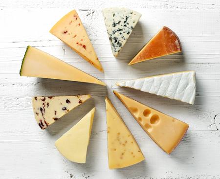 különböző típusú sajtok, fehér fából készült asztal, felülnézet Stock fotó