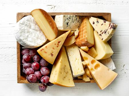 Vari tipi di formaggi in scatola di legno sulla tavola di legno bianca, vista dall'alto Archivio Fotografico - 67181896