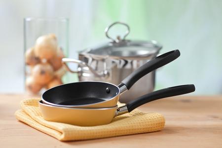 steel pan: el equipo de cocina en la mesa de cocina de madera