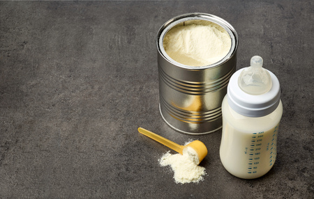 Baby bottle and milk powder on dark grey table