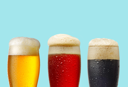 vasos de cerveza: light, red and dark beer glasses on blue background Foto de archivo