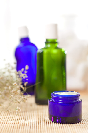 glass jars: green and blue glass bottles on table Stock Photo