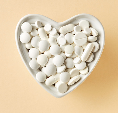 heart shaped bowl of white pills on beige paper background, top view