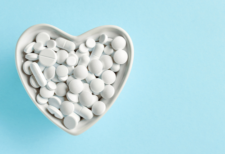 heart shaped bowl of white pills on blue background, top view