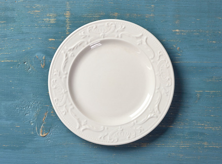 empty plate: white empty plate on blue wooden table, top view
