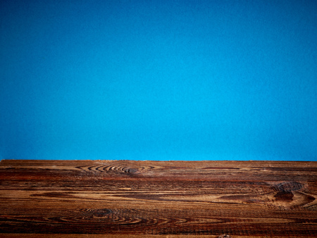 craft material: brown wooden table and blue background