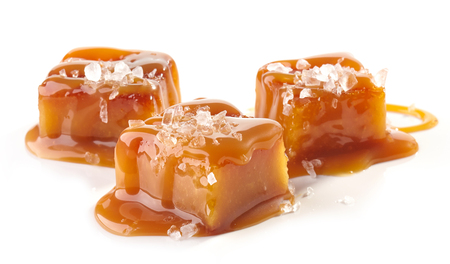homemade salted caramel pieces isolated on white background Imagens