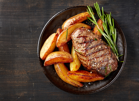 angus: plate of grilled beef steak and potatoes on dark table, top view Stock Photo