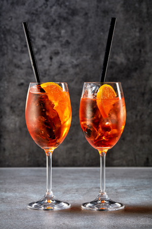 spritz: two glasses of aperol spritz cocktail on grey table Stock Photo