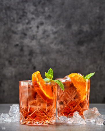 two glasses of aperol soda cocktail and ice cubes on grey table