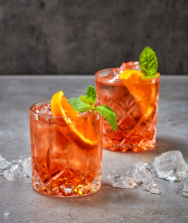 two glasses of aperol soda cocktail on grey table