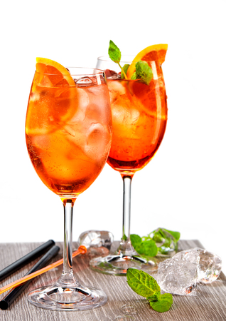 two glasses of aperol spritz cocktail and ice cubes on grey table