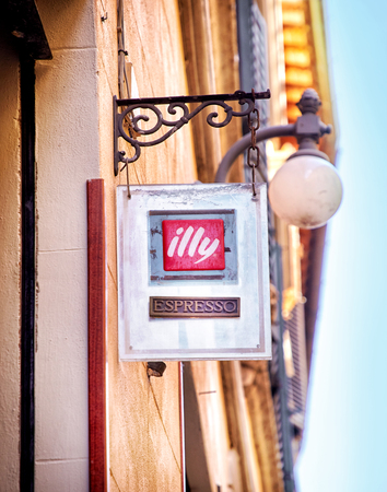 specializes: Montepulciano, Italy - MAY 5, 2017: Signboard of coffee Illy in Montepulciano.  Illycaffe is an Italian coffee roasting company that specializes in the production of espresso Editorial