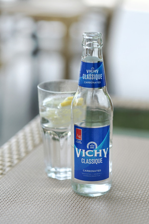 Riga, Latvia - JUNE 18, 2017: Popular latvian carbonated water Vichy in glass and bottle on the table, selective focus