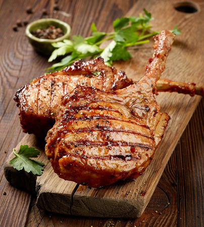 freshly grilled steaks on wooden table