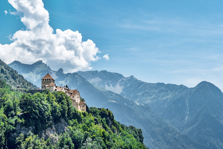Vaduz Castle, the official residence of the Prince of Liechtenstein, with Alps mountains in background Banco de Imagens - 83420910