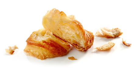Croissant pieces and crumbs isolated on white background