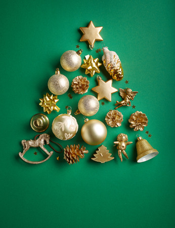 Christmas tree of gold color decorations on green paper background, top view