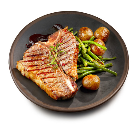 freshly grilled T bone steak and vegetables on dark plate