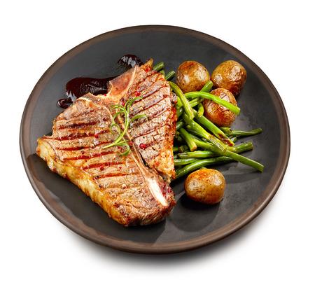 freshly grilled T bone steak and vegetables on dark plate