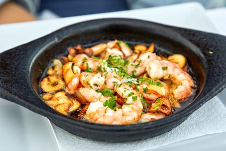 Pan of Garlic Prawns on restaurant table Stock Photo
