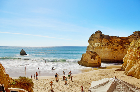 Alvor, Portugal - October 22, 2017: People are swimming and sunbathing at beach of Algarve, Portugal