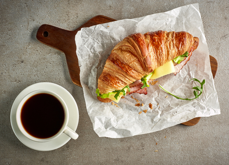 Croissant with ham and cheese on grey table, top view