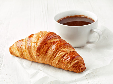 freshly baked croissant and coffee cup on white wooden table